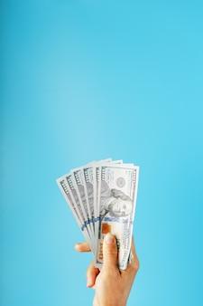 Liasse de billets en main sur bleu