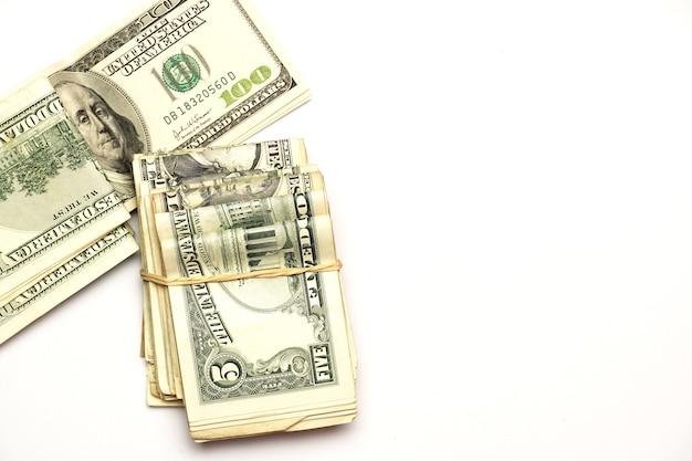 Liasse de dollars à côté d'un billet de cent dollars sur un téléphone blanc concept économique à plat