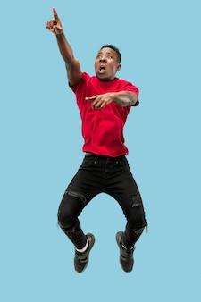Liberté d'avancer et d'avancer l'heureux jeune homme afro surpris sautant