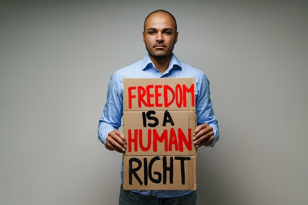 `` la liberté est un droit de l'homme '' pancarte dans les mains de l'homme manifestant sur fond gris
