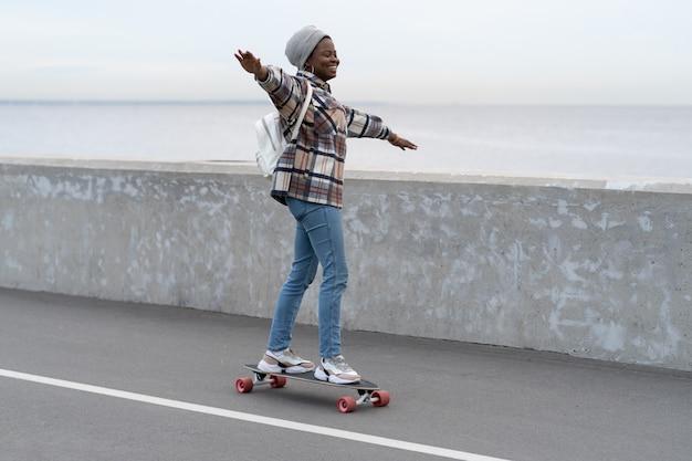 Liberté et mode de vie urbain jeune fille faisant de la planche à roulettes sur un longboard sur une route de la ville ou sur un pont près de la mer