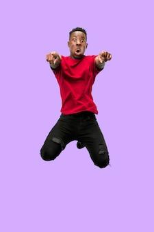 Liberté de mouvement et de mouvement vers l'avant. l'heureux surpris jeune homme africain sautant un fond de studio bleu. runnin man en mouvement ou en mouvement. émotions humaines et expressions faciales