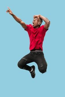 Liberté de mouvement et de mouvement vers l'avant le jeune homme afro surpris heureux sautant