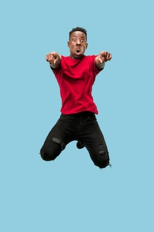 Liberté de mouvement et de mouvement vers l'avant. le jeune homme afro surpris heureux sautant