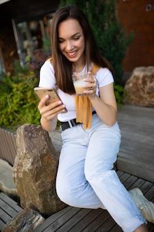 Libre jeune femme buvant du café et bavardant dans un smartphone assis sur un banc dans un parc d'été.