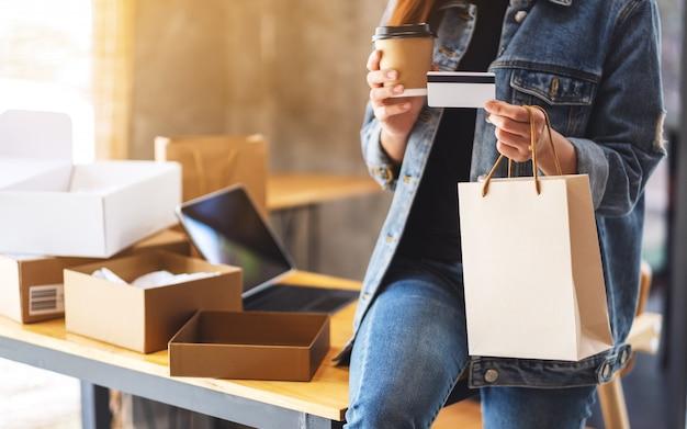 Libre d'une jeune femme tenant et en utilisant la carte de crédit pour les achats en ligne avec tablet pc et colis postal sur la table