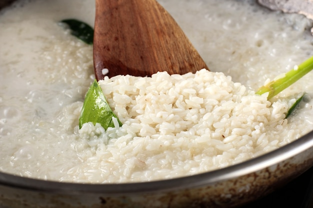 Libre d'une spatule au-dessus d'une casserole de riz gluant bouillant sur un processus de cuisinière un chef making sticky