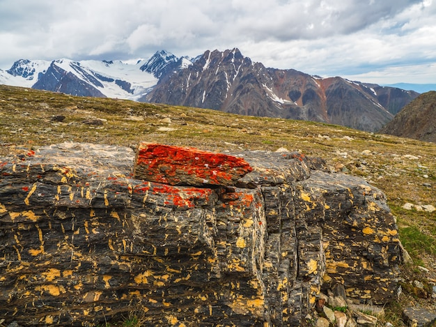 Lichen rouge sur la pierre. lichen sur une pierre en gros plan. pierre brute multicolore au soleil. texture naturelle avec espace de copie. minéral incroyable. morceau de roche.