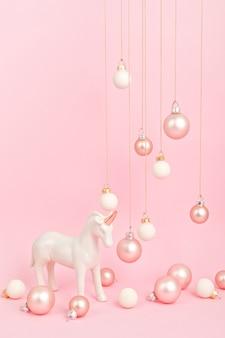 Licorne avec des ornements de noël sur une surface rose