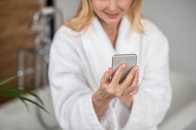 Lié. une femme dans un peignoir blanc avec un smartphone dans ses mains