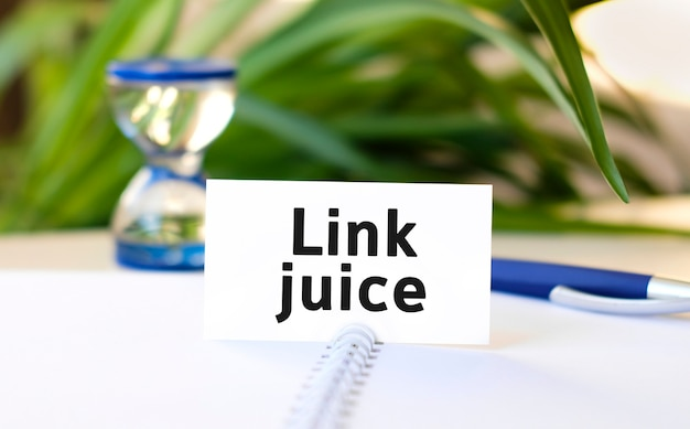 Lien texte de concept d'entreprise seo jus sur un cahier blanc et un sablier, stylo bleu, fleurs vertes