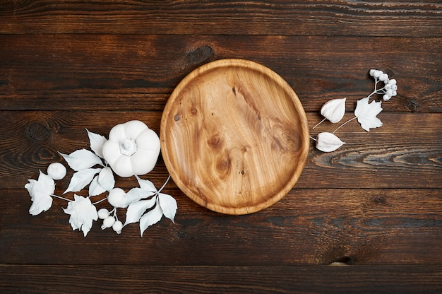 Lieu en bois avec des baies blanches et des feuilles sur une maquette en bois fond d'automne.