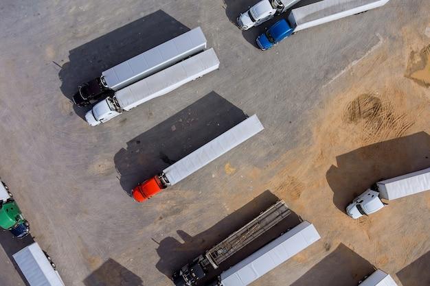 Lieu de repos avec divers types de camions dans un parking bondé près de l'autoroute inter-états