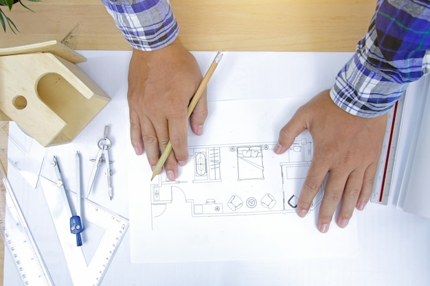 Lieu de travail de l'architecte. architecte travaillant sur plan au bureau