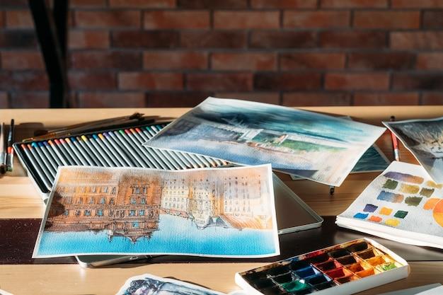 Lieu de travail de l'artiste. atmosphère d'atelier de peintre. aquarelles et fournitures d'art autour.