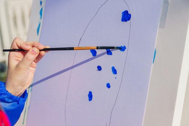 Lieu de travail de l'artiste. un enfant peint à la gouache bleue une image. atelier en plein air