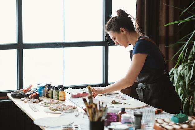 Lieu de travail de l'artiste. inspiration. oeuvre en céramique en cours. femme avec des outils de modélisation travaillant en studio.