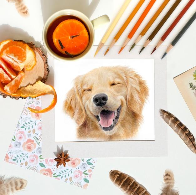 Lieu de travail de l'artiste. matériel d'art et portrait d'un chien labrador. thé et mandarine sur la table