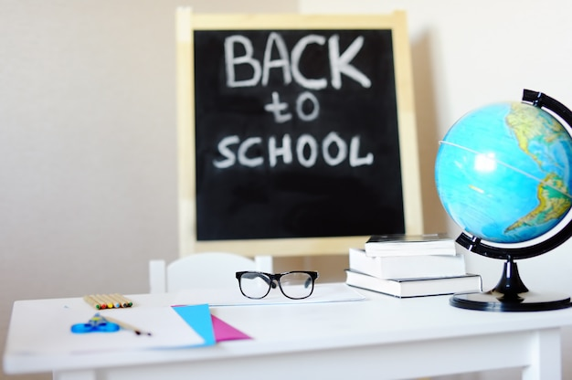 Lieu de travail avec banc d'école, tableau noir, globe et lunettes de vue.
