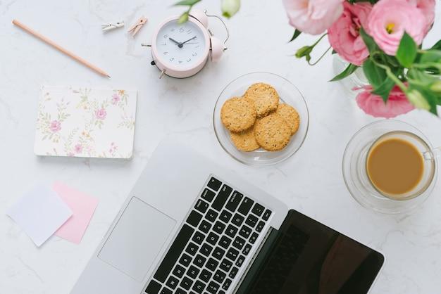 Lieu de travail de la belle femme. ordinateur portable, biscuits, fleurs. mise à plat.