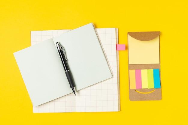 Lieu de travail, bloc-notes, notes autocollantes et stylo sur jaune vif