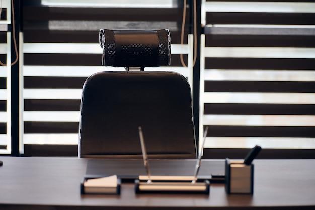 Lieu de travail de bureau d'affaires. lieu de travail pour chef, patron ou autres employés. table et chaise confortable. lumière à travers les stores à moitié ouverts