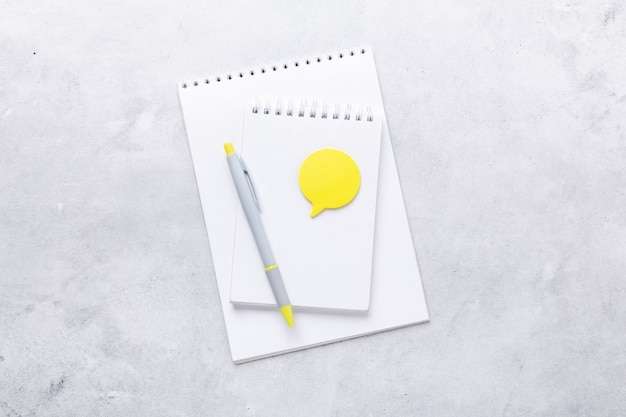 Lieu de travail de bureau. bloc-notes avec stylo et autocollant jaune sur fond de pierre grise. mise à plat. vue de dessus - image