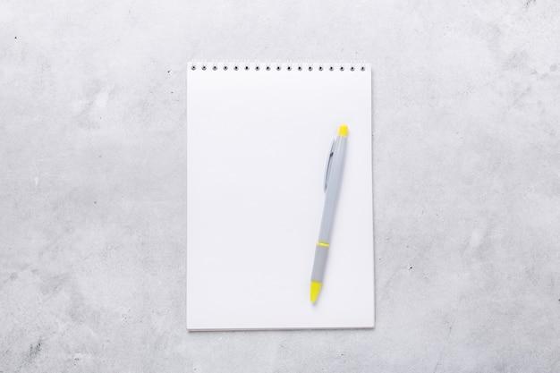 Lieu de travail de bureau. bloc-notes avec stylo sur fond de pierre grise. mise à plat. vue de dessus - image