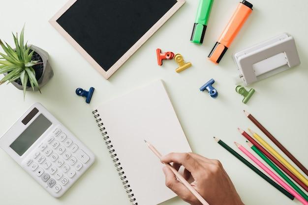 Lieu de travail de bureau - bloc-notes vide, stylo, crayon, règle, boussole sur fond de bois foncé
