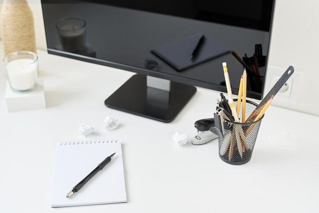 Lieu de travail avec bureau, fournitures de bureau et branche de fleur dans un vase