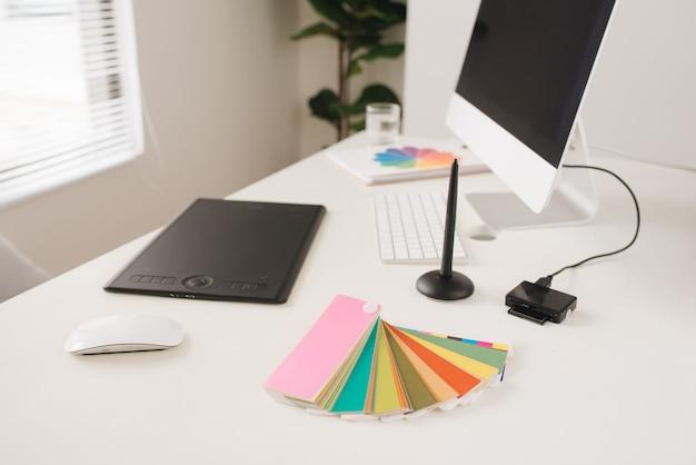 Lieu de travail de bureau moderne avec ordinateur de bureau, stylet et tablette pour la retouche