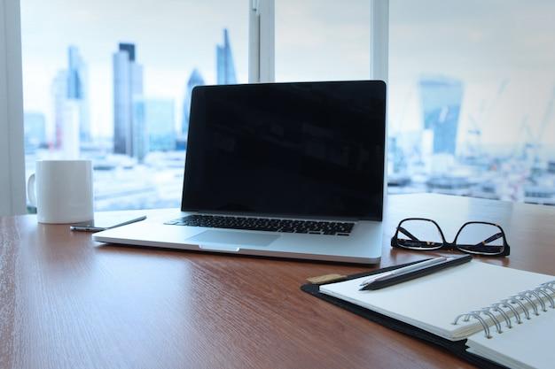 Lieu de travail de bureau avec ordinateur portable à écran blanc et téléphone intelligent sur une table en bois