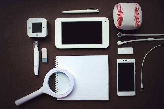 Lieu de travail de bureau avec ordinateur portable, ordinateur portable, fournitures de bureau et papeterie sur fond marron foncé. solution, planification d'entreprise, création, conception, apprentissage, démarrage ou travail à plat sur le concept de vue de dessus.
