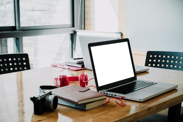 Lieu de travail de bureau avec ordinateur portable portable écran blanc tableau de travail confortable dans la fenêtre de bureau