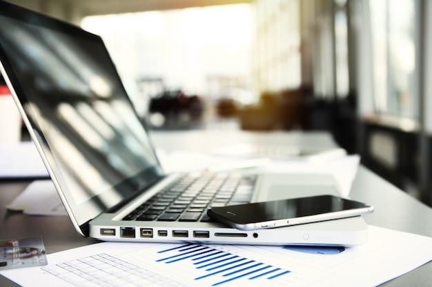 Lieu de travail de bureau avec ordinateur portable sur table en bois contre les fenêtres.