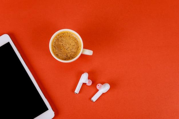 Lieu de travail de bureau avec tablette numérique sur un casque sans fil une tasse de café sur fond rouge