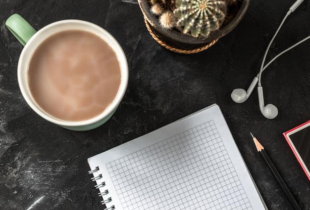 Lieu de travail avec cahier ouvert et crayon, tasse à café, écouteurs, lecteur de musique et cactus sur un bureau noir