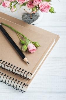 Lieu de travail avec des cahiers et des roses