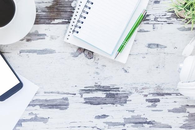 Lieu de travail avec des cahiers et un smartphone près de tasse à café