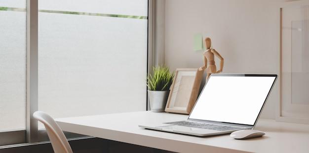 Lieu de travail confortable avec un ordinateur portable à écran blanc ouvert