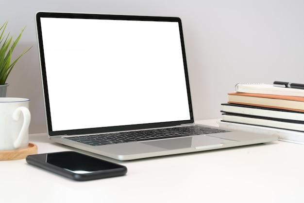 Lieu de travail confortable avec un ordinateur portable à écran blanc sur une table au bureau