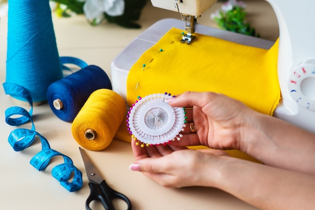 Lieu de travail de la couturière. machine à coudre professionnelle au travail. la machine à coudre coud des textiles brillants, du mètre et des fils colorés pour la couture