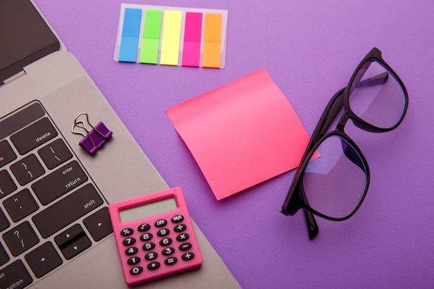 Lieu de travail créatif avec calculatrice, ordinateur portable, lunettes et pense-bête rose.