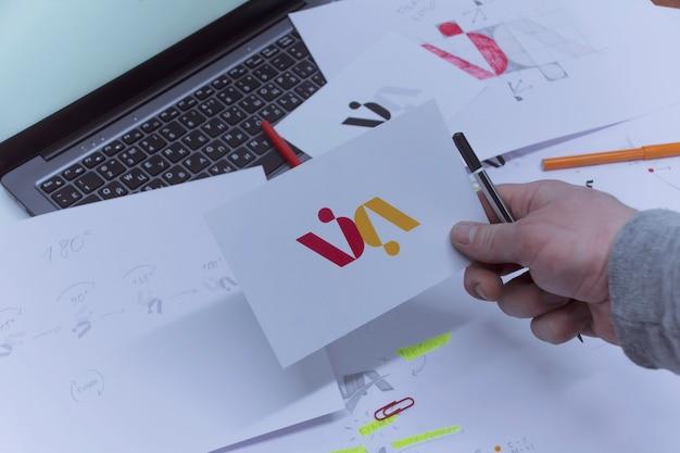 Lieu de travail créatif d'un graphiste. un homme au bureau développe un logo sur la table sur fond de croquis imprimés et d'un ordinateur portable.