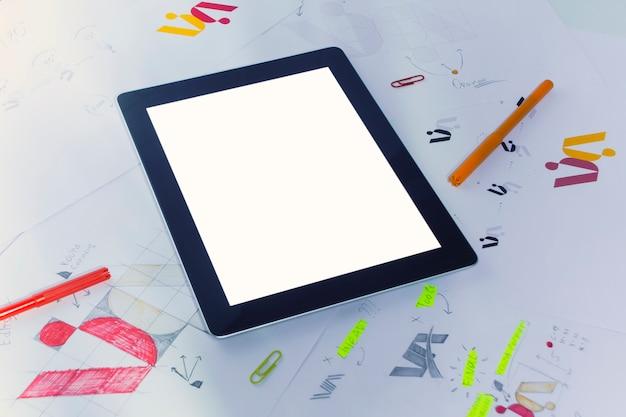 Lieu de travail créatif d'un graphiste avec tablette. développement d'un logo pour l'entreprise. dessins et croquis sur papier dans un bureau d'atelier d'art.