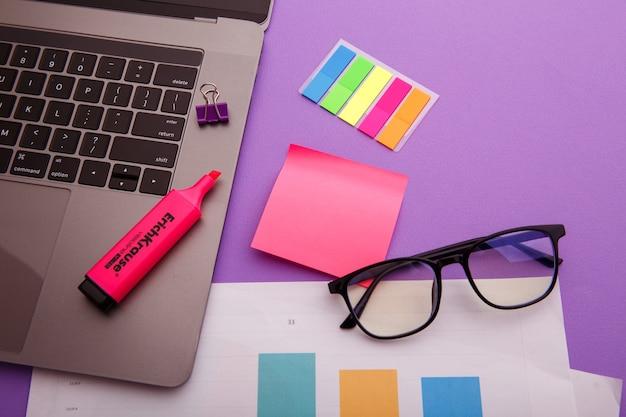 Lieu de travail créatif avec ordinateur portable, lunettes et pense-bête rose.