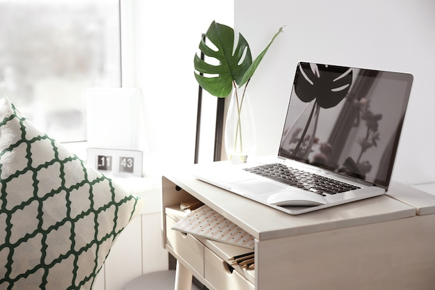 Lieu de travail créatif avec ordinateur portable près du rebord de la fenêtre dans une salle moderne
