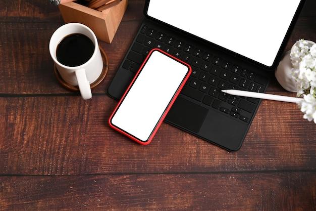 Lieu de travail design avec tablette informatique, téléphone portable, tasse à café et porte-crayon sur table en bois.