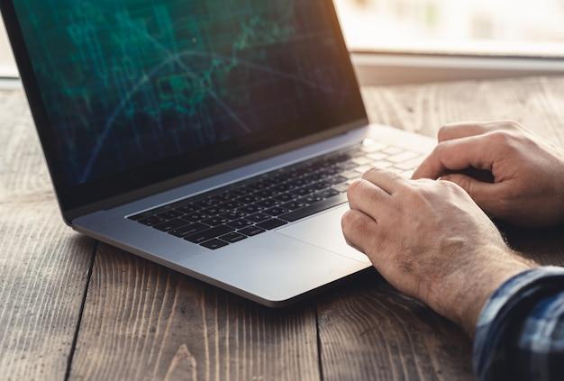 Lieu de travail à domicile. homme regardant graphique sur analyse d'ordinateur portable assis dans le bureau à domicile