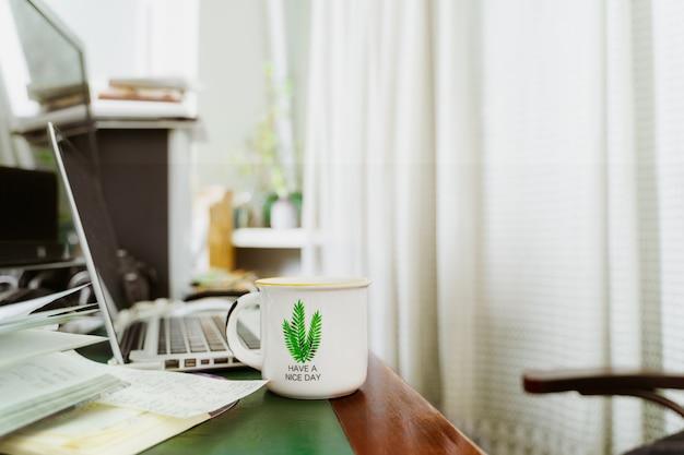 Lieu de travail à domicile avec ordinateur portable ouvert, papiers et une tasse de thé sur un bureau en bois